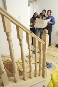 Couple and contractor looking at plans for unfinished stairs