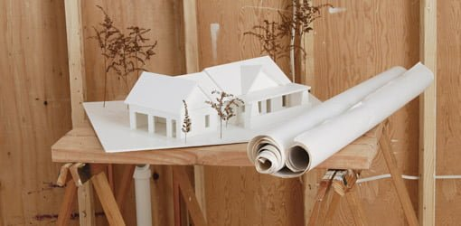 Paper model of house with plans on sawhorses