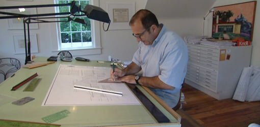 Architect working at drawing board.