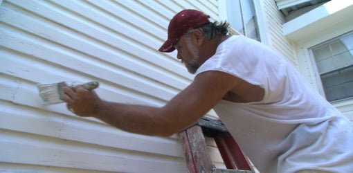 Painter painting siding with brush.