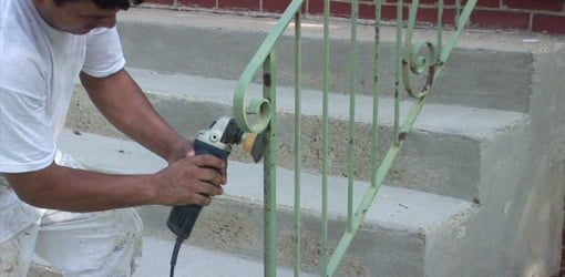 Using grinder with wire brush to remove rust from metal handrails.