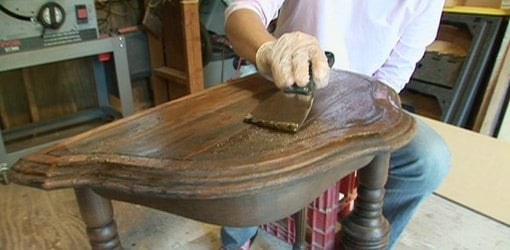 Removing finish from table top.
