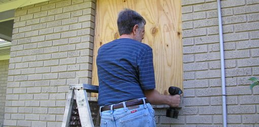 Boarding up windows with plywood before a hurricane.