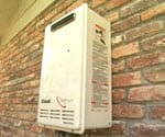 Tankless hot water heater mounted outside on brick wall of home.
