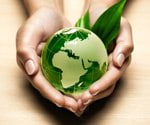 Hands holding green Earth.