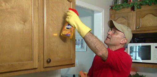 Joe Truini using hot sponge to clean grease off kitchen cabinets.