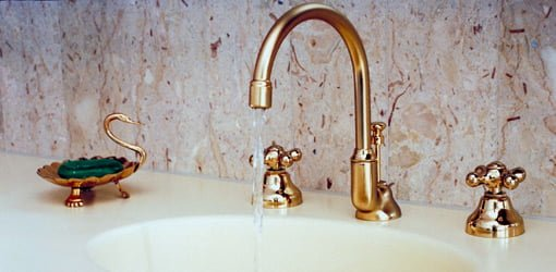 Bathroom faucet with water running.