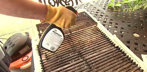 Using grill cleaner to clean the cooking grates on a gas grill.