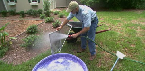 Cleaning window screens using a kiddie pool, garden hose, and broom.