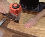 Attaching mitered molding to stained plywood cabinet doors.