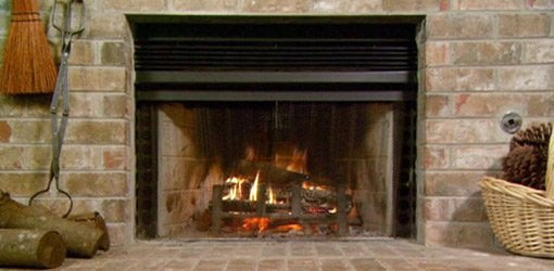 Fireplace with fire burning inside.