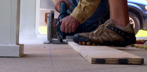 Using circular saw to score grooves in concrete.