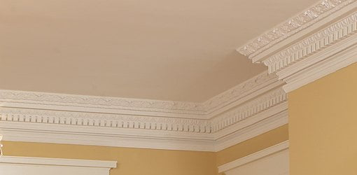 Decorative white crown molding around ceiling in room with yellow walls.