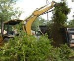 Backhoe removing landscaping debis from around house