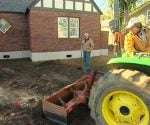 Tractor grading lot at the Kuppersmith Project house