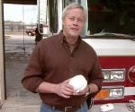 Danny Lipford standing by fire truck holding smoke detector.