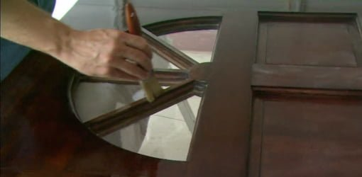 Applying clear finish to an entry door.