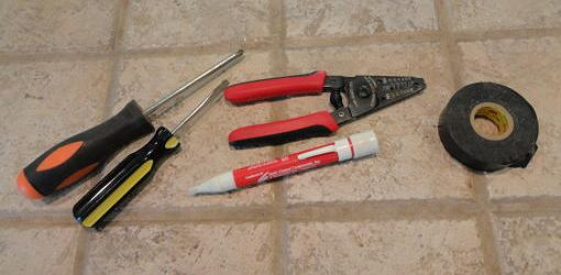 Screwdrivers, stripping pliers, voltage tester, and electrical tape
