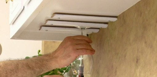 Sliding wine glass onto homemade rack mounted under hanging kitchen cabinet