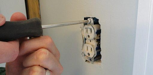 Unscrewing an electrical outlet from the box