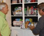 Homeowner Bud Black and Allen Lyle installing roll-out wire baskets in kitchen cabinets