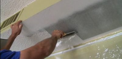 Scraping popcorn texture off ceiling with drywall knife.