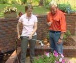 Julie Day demonstrating plant watering to Danny Lipford.