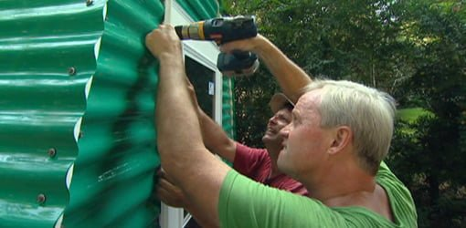 Danny Lipford and Allen Lyle attaching the door to the greenhouse.
