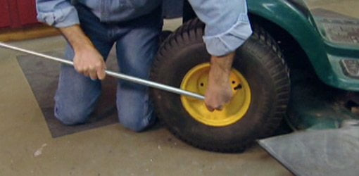 Using a pipe for a socket wrench tool handle extension to loosen a bolt on a lawn mower tractor tire.