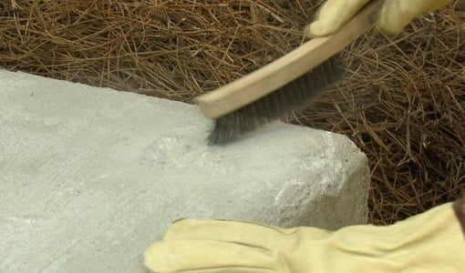Using wire brush to remove loose concrete material