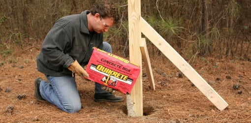 Pouring dry concrete mix into a hole around a wood post.