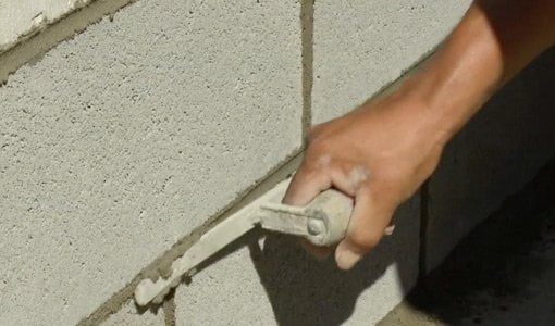Using a jointing tool to smooth mortar joints in concrete block wall.