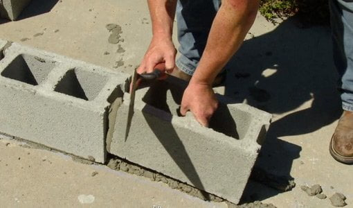 Laying concrete block in row with buttered end.