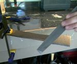 Sharpening lawn mower blade with file.