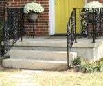 Refinished and repaired metal handrails on porch.