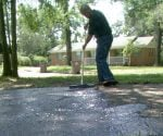 Danny Lipford applying asphalt sealer to driveway.