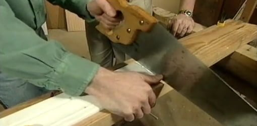 Cutting molding clamped to scrap board with handsaw.