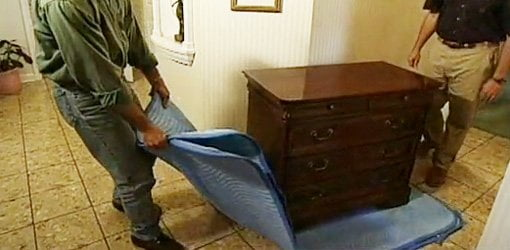 Using a moving pad or blanket to slide heavy furniture across the floor.
