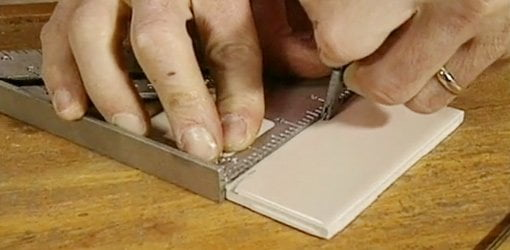 Scoring ceramic tile with a glass cutter to cut the tile to size.
