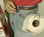 Drywall tape roll holder made from wire hanger hooked on belt.