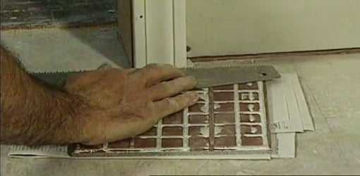 Using a handsaw on top of a tile spacer to cut door casing for a tile floor.