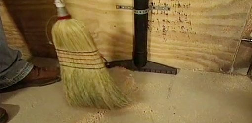 Sweeping sawdust into shop vac floor nozzle mounted on wall.