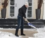 Shoveling snow on sidewalk in front of house.