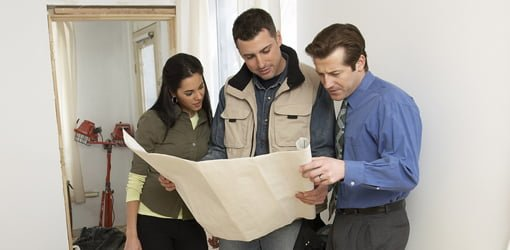 Homeowners and contractor looking over plans for home improvement project.