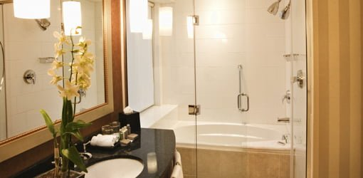 Bathroom with shower surround around tub and glass doors.