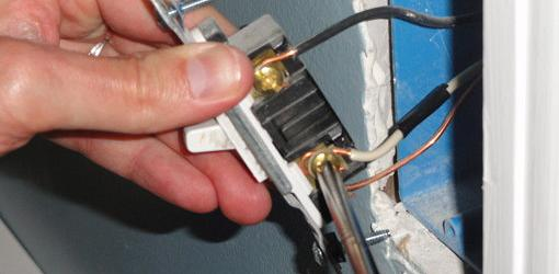 Attaching wires to a wall switch.