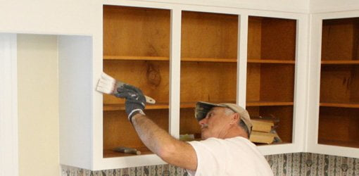 Painter priming kitchen cabinets.
