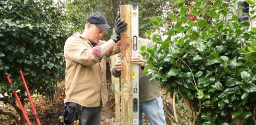 Plumbing and aligning fence posts in holes.