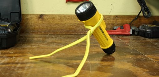 Flashlight stand made from electrical cable.