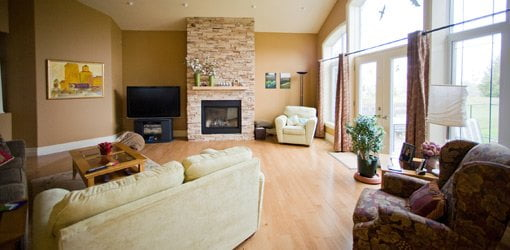 Living room with fireplace and wall of windows.